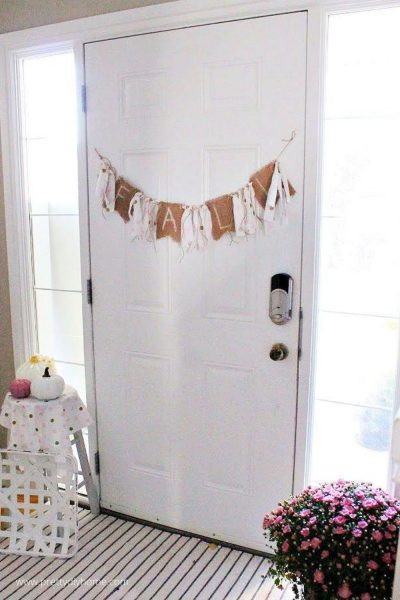 A front door decorated for Fall with a DIY pink and burlap Fall rag banner, pink flowers and pink pumpkins.