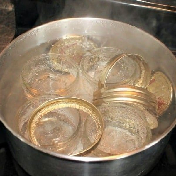 A large pot of boiling water for sterilizing jars and lids for canning homemade apple butter.