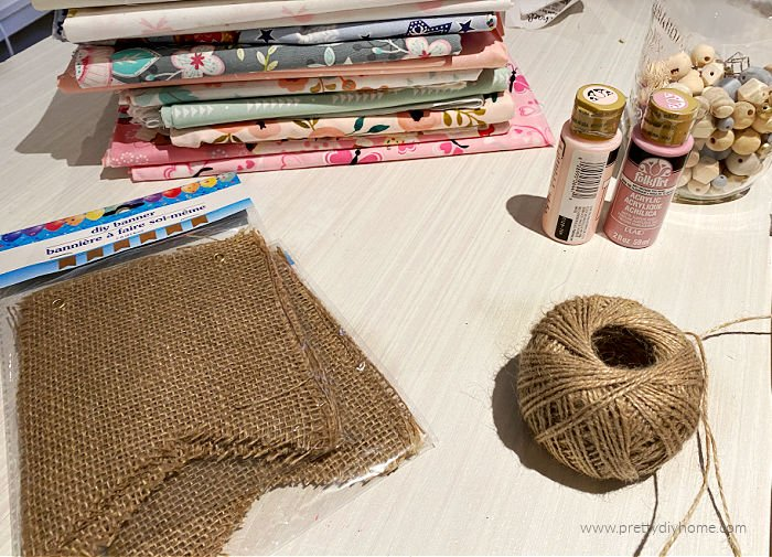 Dollar Tree Craft supplies including a burlap banner, twine, pink paint, and bits of fabric.
