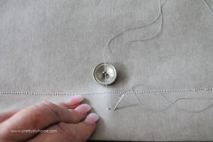 Sewing a button onto a DIY envelope cushion with a needle and thread.