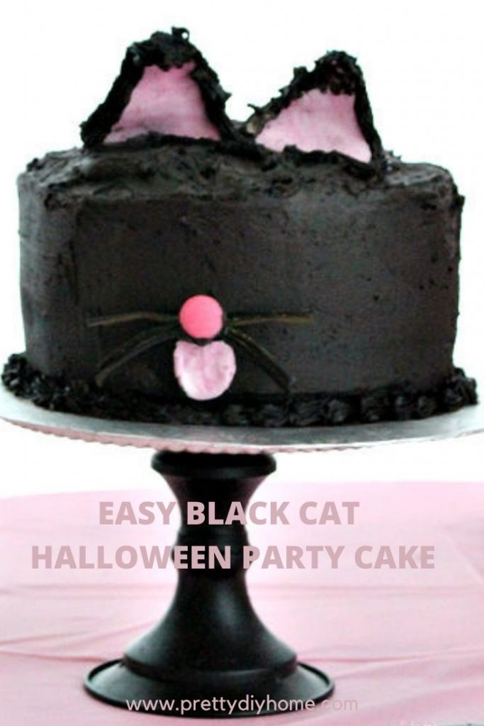 A not scary easy black cat cake on a black pedestal for a Halloween party. The table is decorated in pink with white pumpkins.