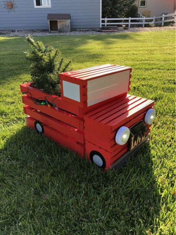 A red truck made out of crates for a front yard ornament.