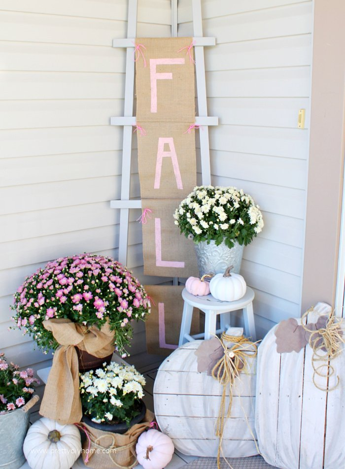 DIY Fall front porch decor with a Fall burlap sign hanging from a ladder, mums, pink and white pumpkins.