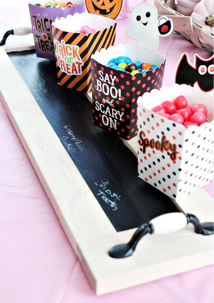 An upcycled drawer front becomes a chalk board serving tray for Halloween candy. The labels are marked on the chalkboard.