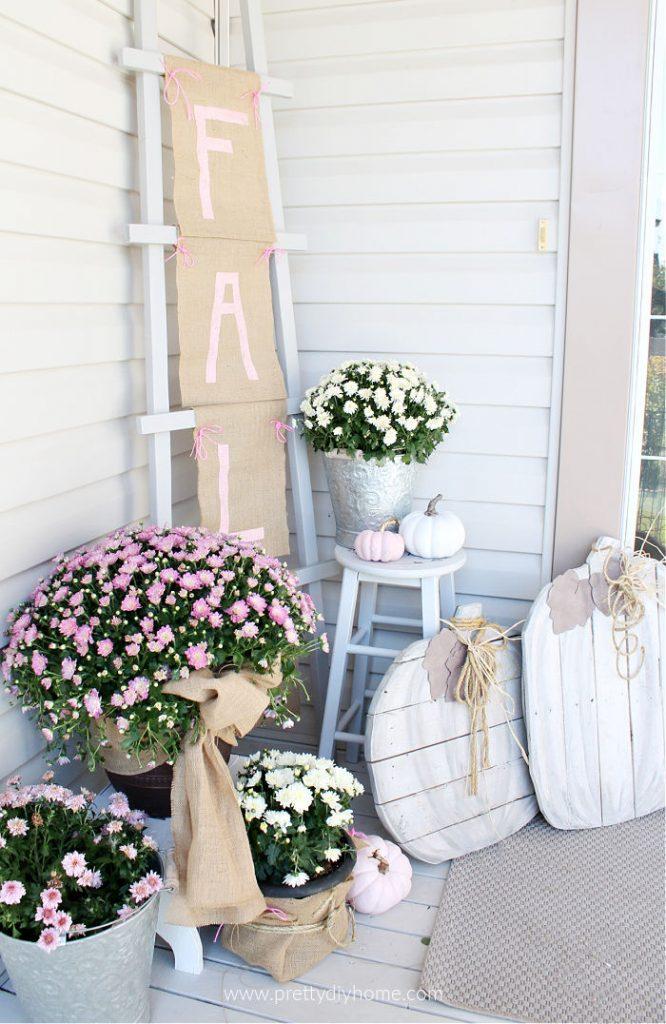 Fall front porch decor with a DIY ladder Fall burlap sign, mums and pumpkins.