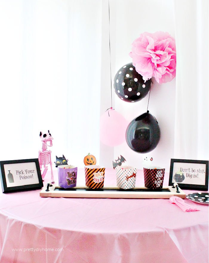 A Halloween party table set with an easy simple Halloween candy buffet.  There are printable Halloween signs in frames and pretty pink and black balloons in the background.