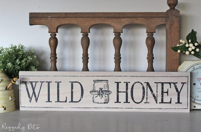 Easy DIY Farmhouse sign in white that says wild honey with a bee motif