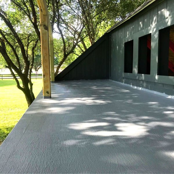 A large DIY plywood deck painted with grey rubber product sealer