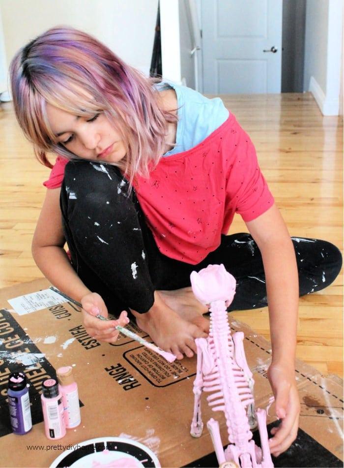 Little girl doing a pink Halloween craft of a cat.