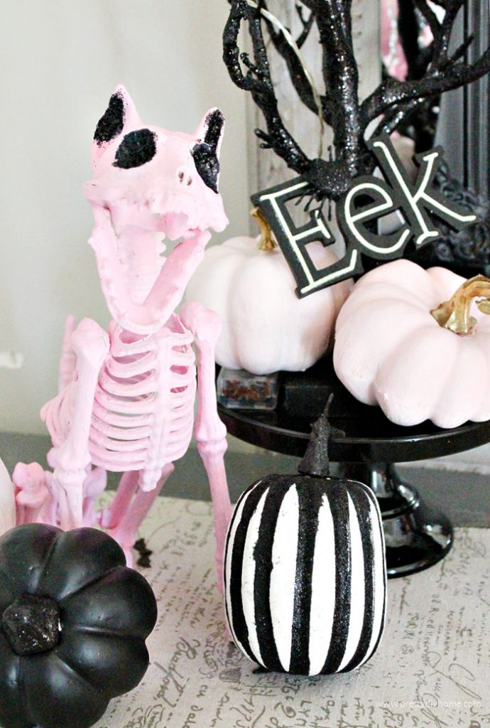 DIY Halloween cat decoration in pink with black glittery eyes. The cat is part of a pretty Halloween display with pink and black pumpkins and fairy lights.