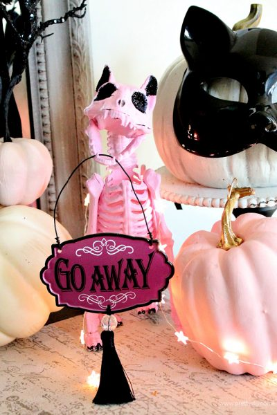 DIY Halloween craft of a pink cat with black sparkles, pumpkins and a haunted house chalkboard in the background.