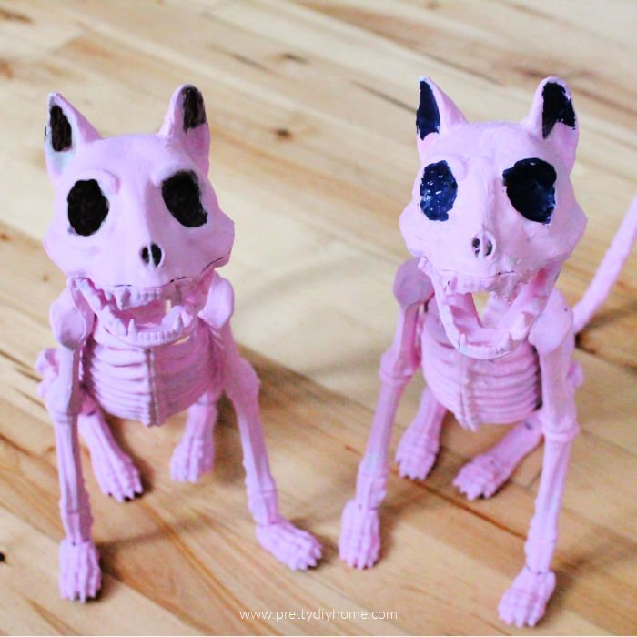 Two matching pink Halloween cats with black eyes.