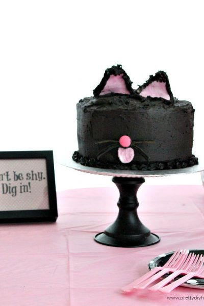 Simple and easy black cat cake with licorice whiskers and pink fondant ears. A not scary Halloween Party cake idea.