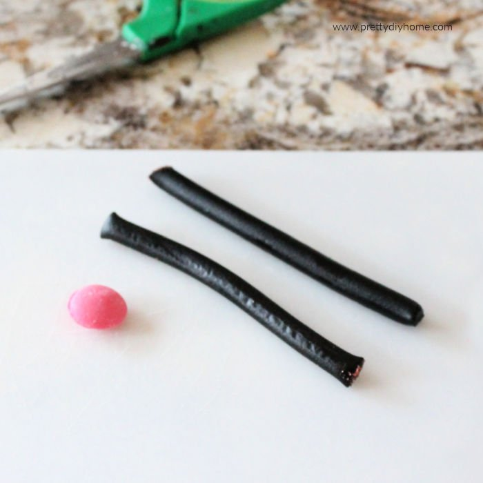 Black licorice cigars and pink candy for making the face on a black cat cake.