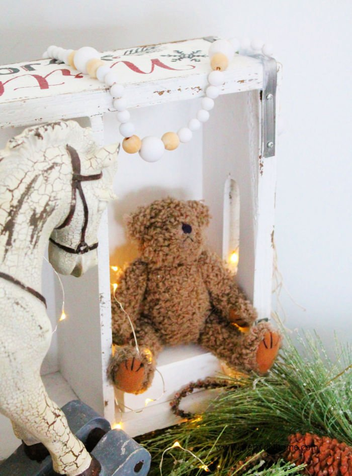 Handmade wooden Farmhouse Bead Garland for Christmas with a teddy bear, vintage boxes and a rocking horse.