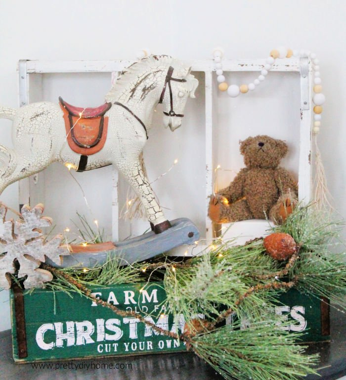 A Christmas display made using vintage toys and a homemade farmhouse wooden bead garland.