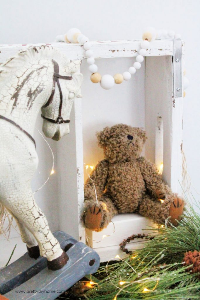 A white and natural bead Farmhouse Garland in a Christmas vignette. A pretty DIY Christmas gift idea.