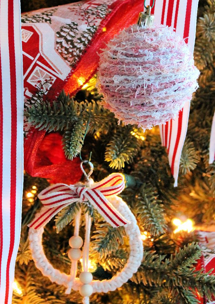 Two different DIY farmhouse Christmas ornaments hanging on a Christmas Tree