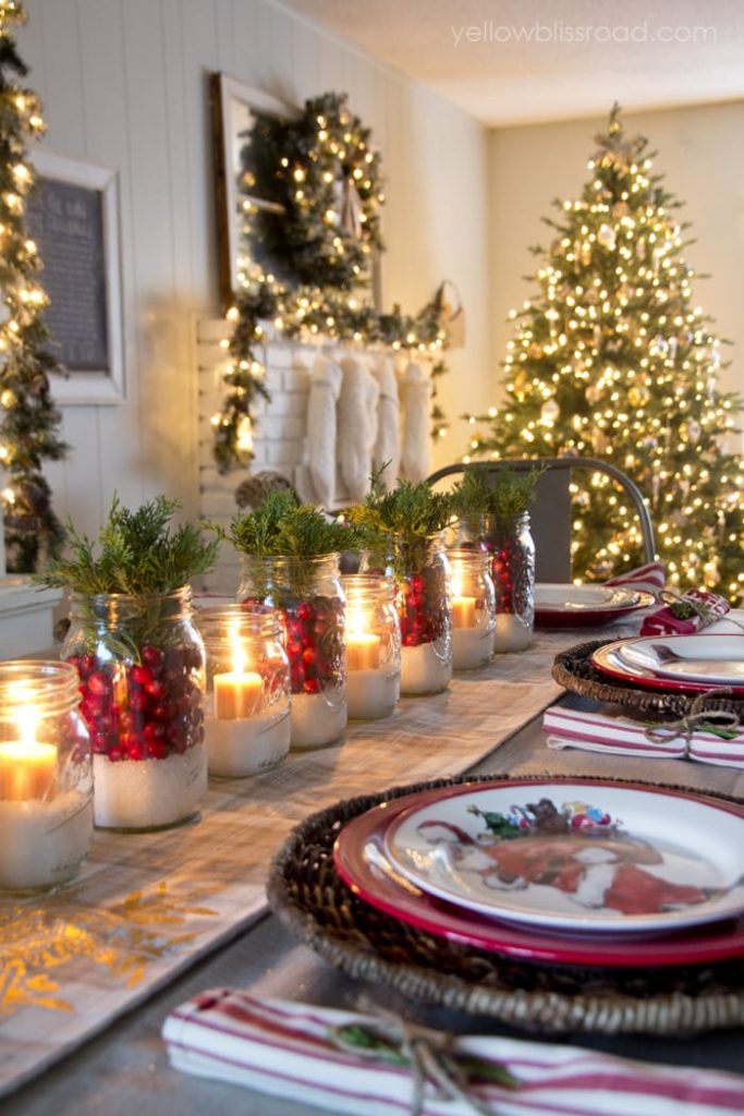 Table set with traditional red and green for Christmas with cranberries, sugar in jars, greenery and a tree in the background.