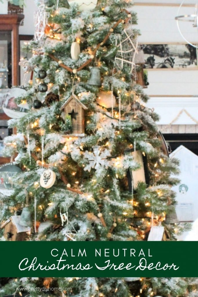 A large neutral farmhouse Christmas tree decorated with barn ornaments, galvanized bells, natural wood birdhouses and large Christmas ornaments.