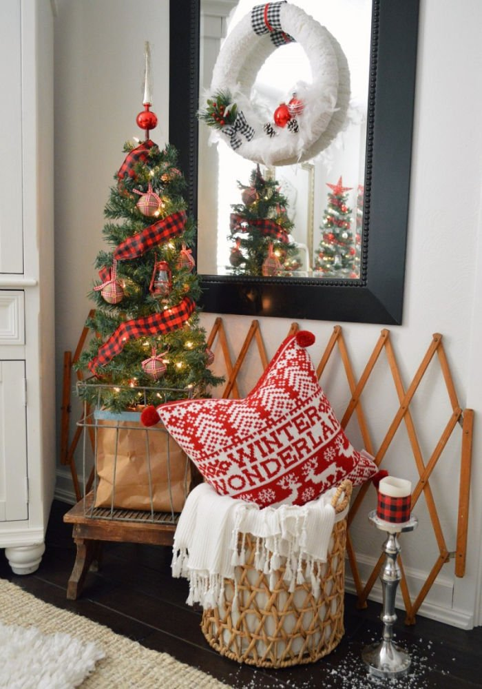 A small front foyer decorated for Christmas with pretty tartan Christmas decorations and cushion,