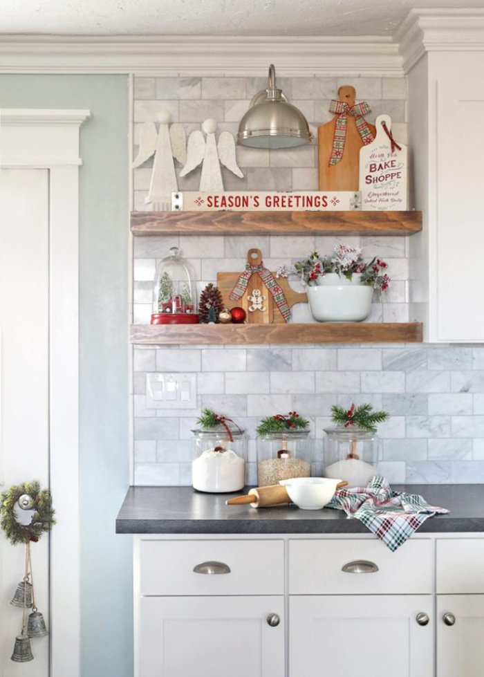 Kitchen shelf decorated for Christmas in white with plaid accessories.