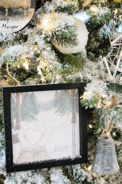 Soft looking Christmas tree ornaments in neutral colors with black frame hanging on a flocked Christmas tree.