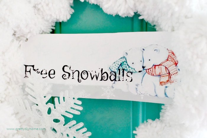 A free printable banner for a wreath that says Free Snowballs, with two cartoon polar bears on a snowball wreath made of woolen pom poms.