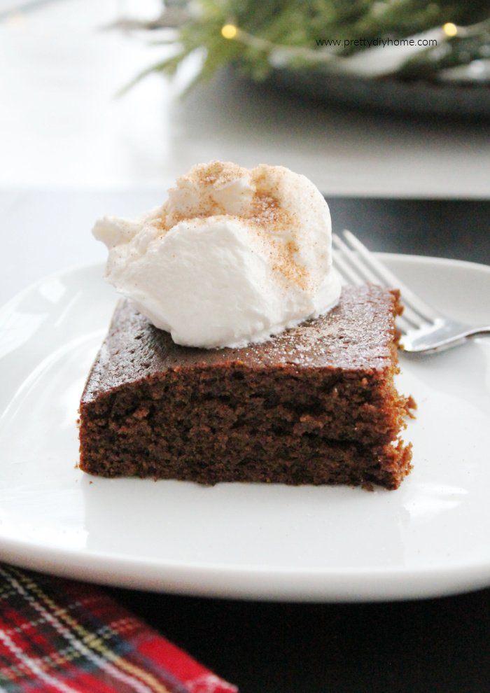 A slice of gingerbread cake served with whipped cream and a sprinkle of cinnamon sugar.