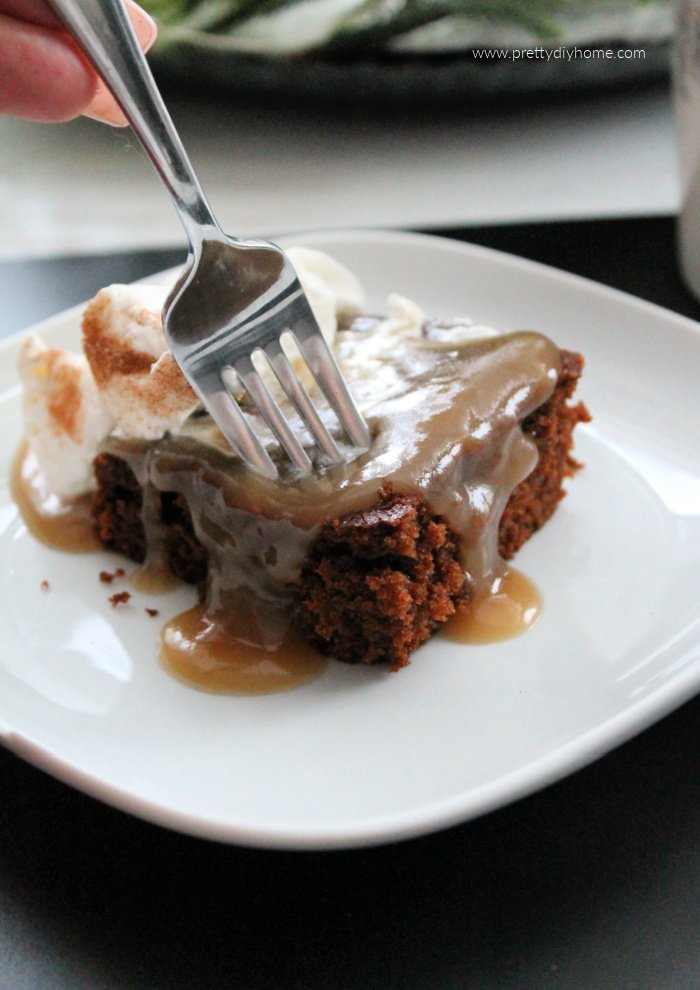 A slice of gingerbread cake with whipped cream and brown sugar sauce.