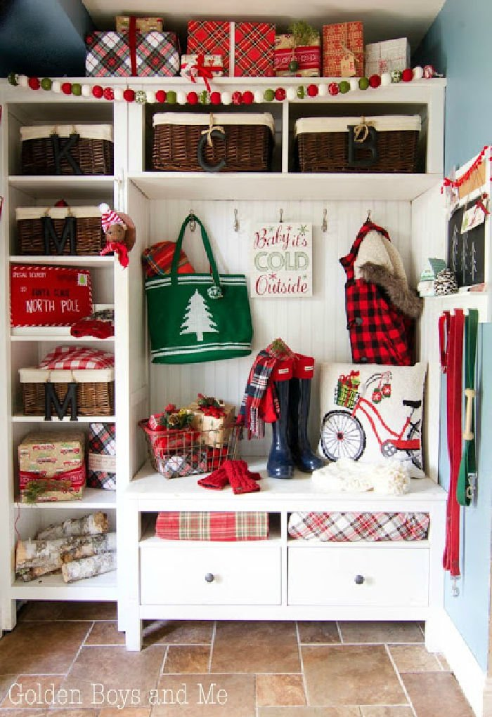 A farmhouse hall tree decorated for Christmas with lots of tartan plaid accessories.