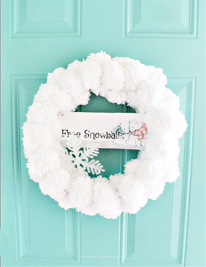 Large white pom pom craft for Christmas. A large DIY Christmas snowball wreath hanging on a front door.