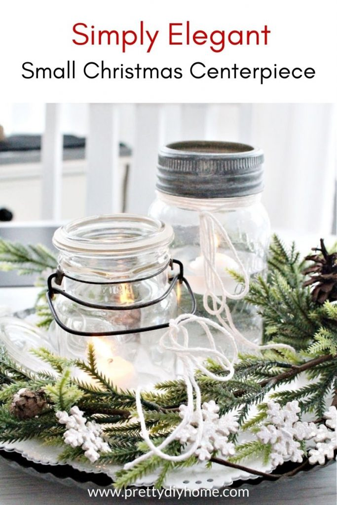 Small Christmas Centerpiece for the Kitchen table with galvanized plate, vintage mason jars, greenery. and sparkling snowflakes.