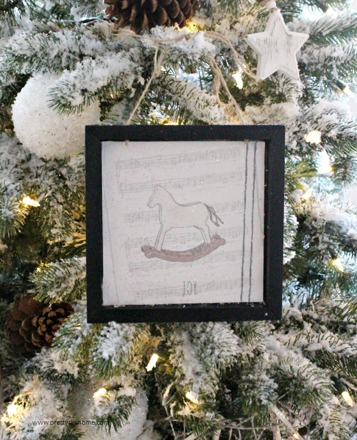 Christmas Tree ornament with a black frame, twine ties and rocking horse pictire.