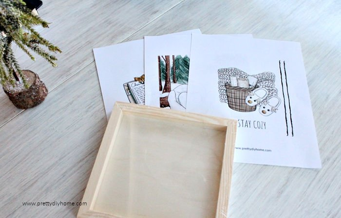 Three different printables and a wood frame. Supplies for making a DIY Christmas Ornament