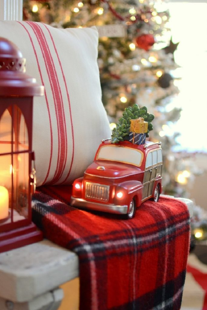 Simple chair decorated with a gorgeous tartan throw, farmhouse cushion and a red truck for the holidays.