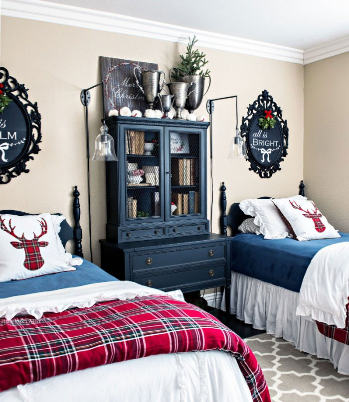 A guest room with twin beds decorated for Christmas with Christmas tartan plaid throws and cushions.