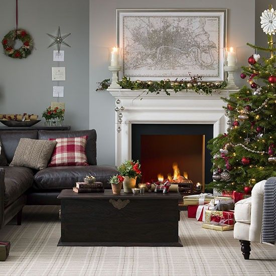 Traditional Christmas decorated living room with Christmas tree, greenery and plaid cushions.