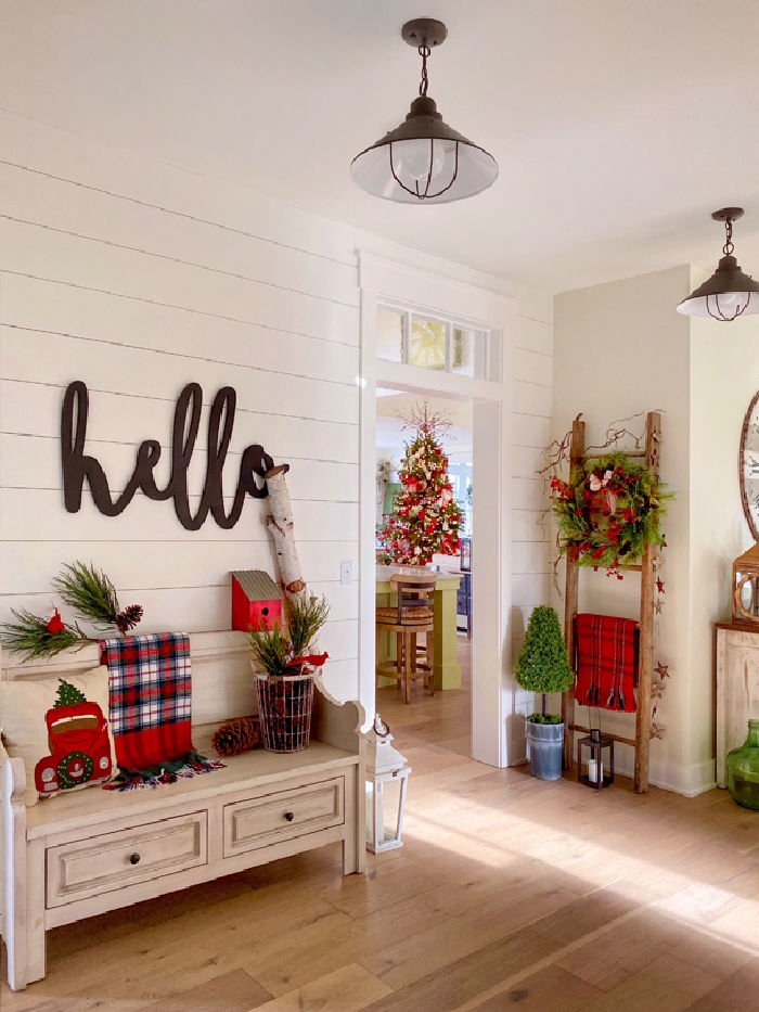 Bright farmhouse style Christmas foyer decorated in tartan plaid for the holidays.