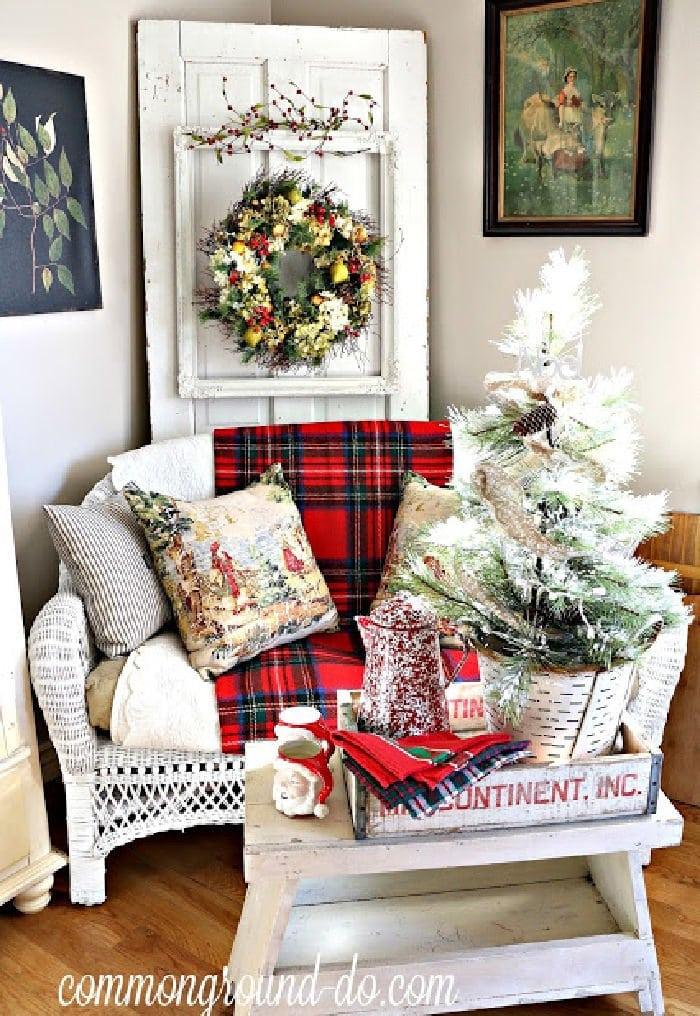 Farmhouse style family decorated with plaid, a pretty Christmas wreath, farmhouse door and DIY bench