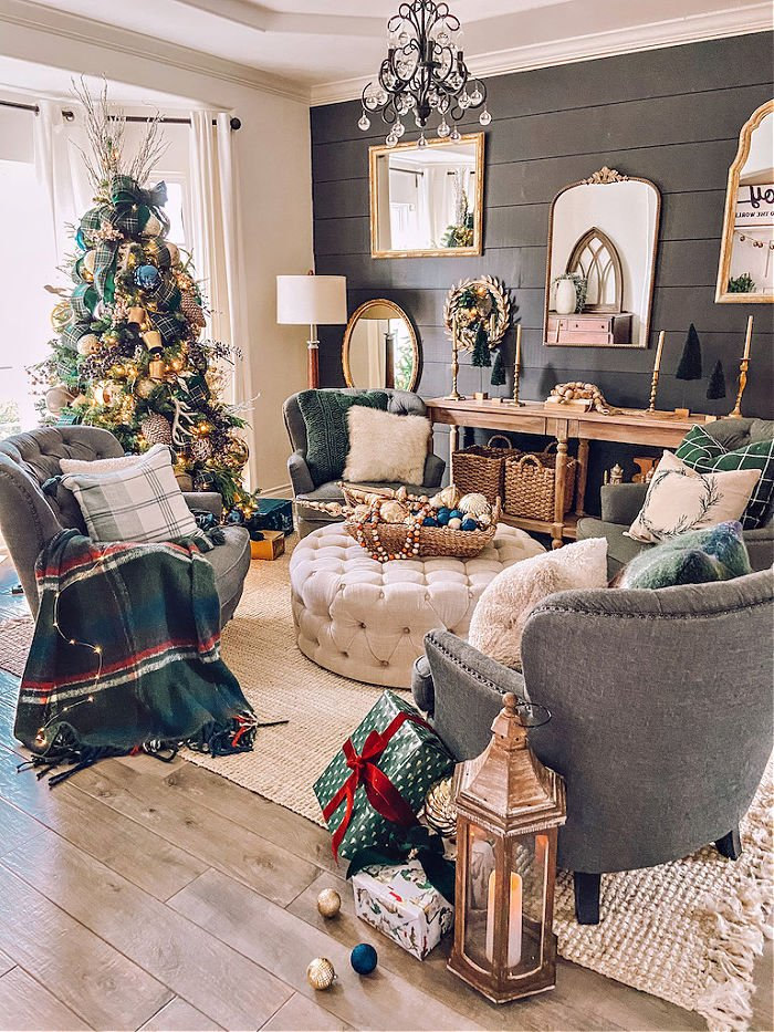 A farmhouse living room decorated for Christmas with a tartan ribbon Christmas tree, tartan throw cushions and antique mirrors on the wall.