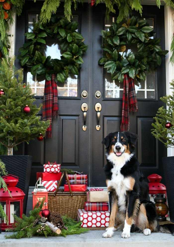 Front Christmas porch with traditional Christmas wreaths, plaid wrapped gifts and a border collie.