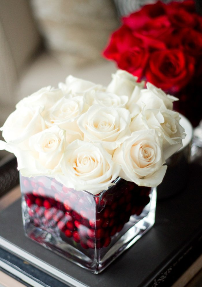 Simple Christmas centerpiece with white roses in a vase filled with red cranberries.