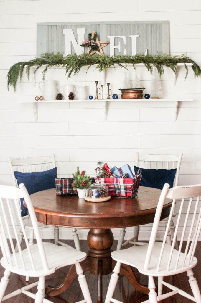 Farmhouse Christmas Dining room with a wood brown table, white chairs and tartan fabric basket centerpiece.