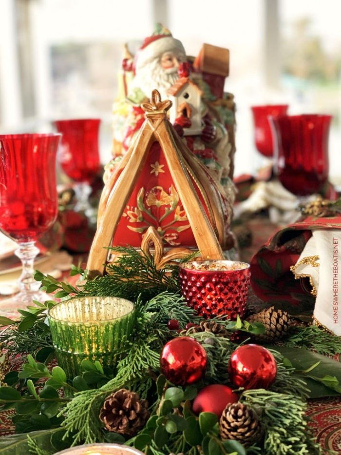 Traditional Christmas table setting with red balls, Santa centerpiece, candles, greenery, plaid tablecloth and red wine glasses.