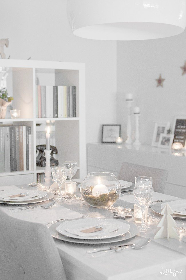 Christmas tablescape with white dishes, and crystal glasses