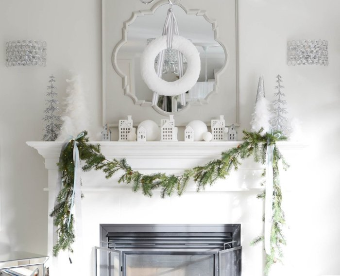 White Christmas decor decorated mantel with a white wreath mirror, white houses and candles.
