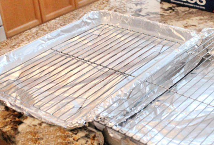 Preparing pans with tin foil and baking cooling racks for making baked wings.