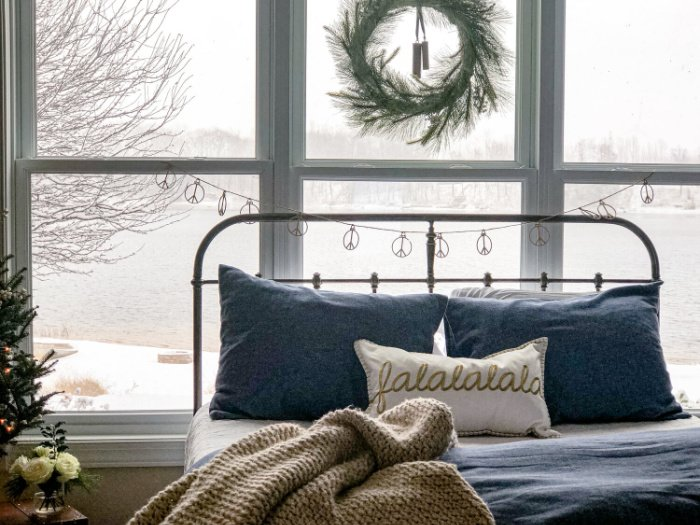 A Christmas bedroom home tour, with a large bed sitting in front of a gorgeous window with an ice covered lake in the background.
