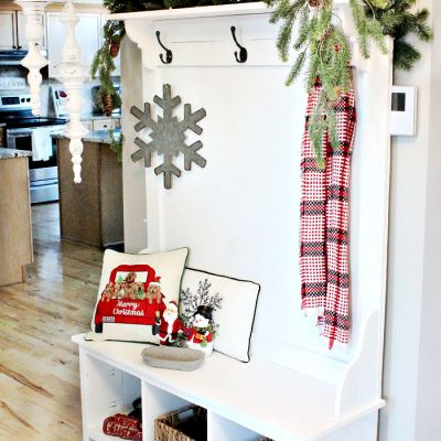 A space saving DIY Farmhouse Christmas hall tree decorated with cushions, greenery, a lantern and Christmas decor.